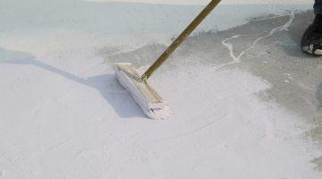 concrete floor sealer being brushed on cellar floor